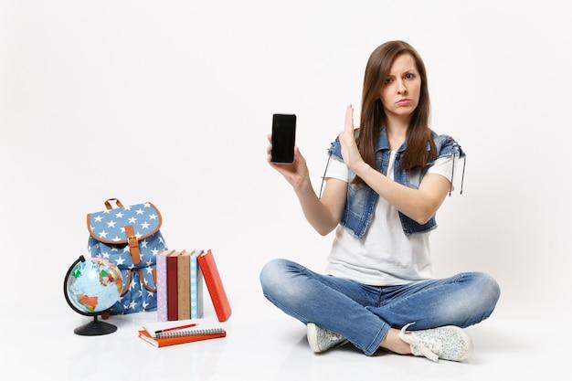 Jovem, intrigada, aluna segura o celular com uma tela preta em branco e mostra o gesto de parada com a palma da mão perto do globo, mochila com livros escolares