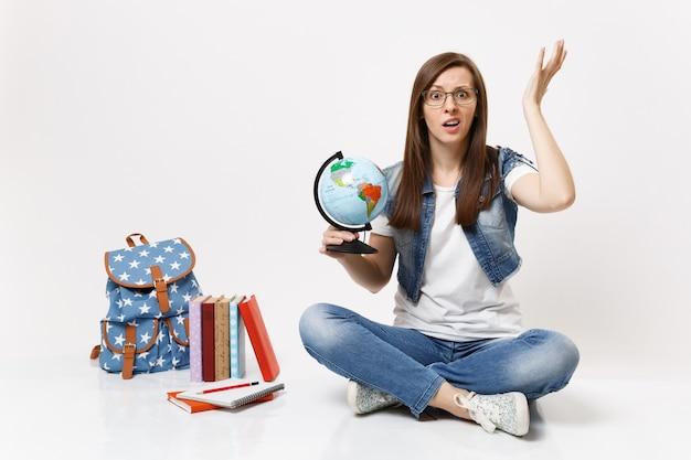 Jovem intrigada e insatisfeita estudante de óculos segurando um globo terrestre, espalhando as mãos, sentada perto de uma mochila, livros escolares isolados