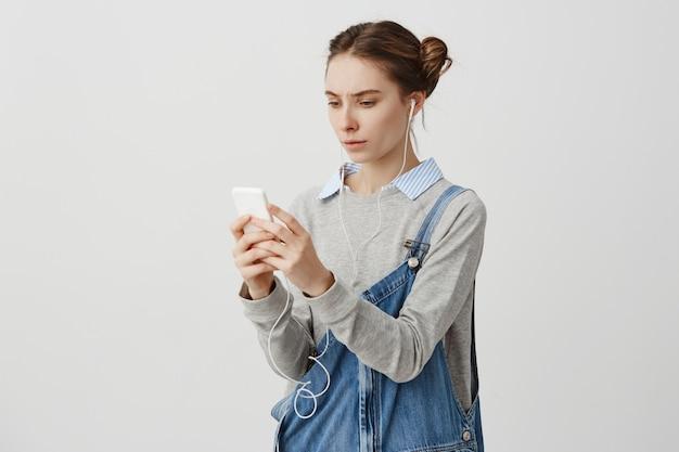 Jovem intrigada em fones de ouvido franzindo a testa tendo problema com o gadget. linda produtora que está decepcionada por causa da falta de conexão à internet em seu telefone. conceito de tecnologia