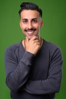 Jovem iraniano bonito com bigode verde