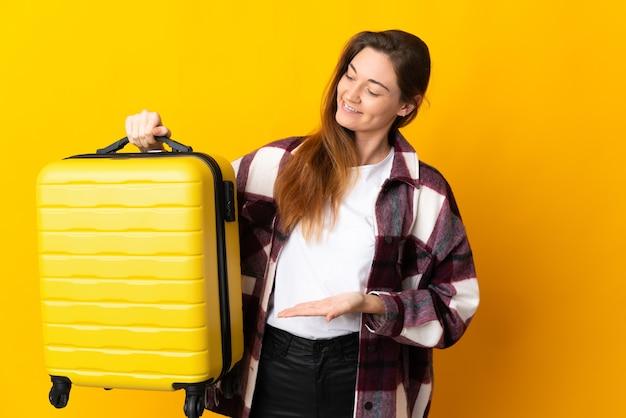 Jovem irlandesa isolada em um fundo amarelo de férias com uma mala de viagem