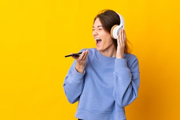 Jovem irlandesa isolada em um fundo amarelo ouvindo música com um celular e cantando