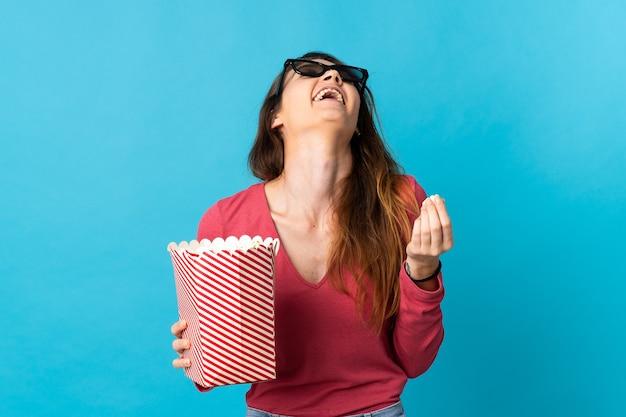 Jovem irlandesa isolada em um fundo azul com óculos 3d e segurando um grande balde de pipocas