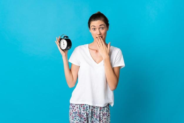 Jovem irlandesa isolada em um fundo azul, de pijama e segurando o relógio com expressão de surpresa