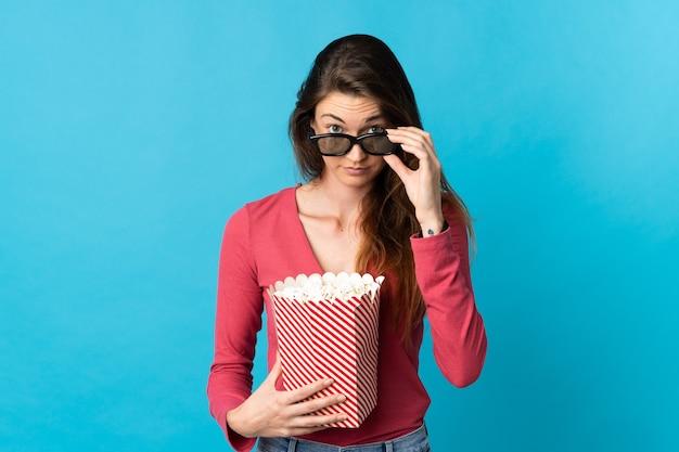 Jovem irlandesa isolada em um fundo azul surpresa com óculos 3d e segurando um grande balde de pipocas