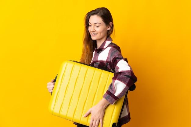 Jovem irlandesa isolada em uma parede amarela de férias com uma mala de viagem
