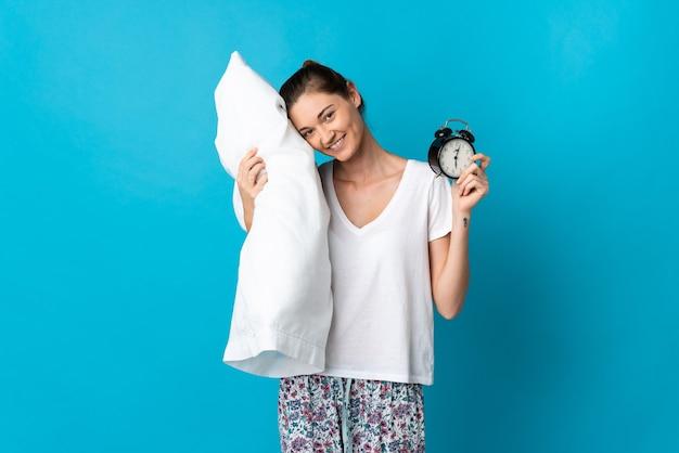 Jovem irlandesa isolada na parede azul, de pijama, segurando o relógio e o travesseiro com uma expressão feliz