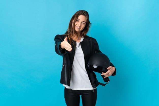 Jovem irlandesa segurando um capacete de motociclista isolado em um fundo azul, apertando as mãos para fechar um bom negócio
