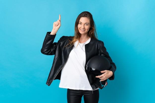 Jovem irlandesa segurando um capacete de motociclista isolado em um fundo azul apontando para uma ótima ideia