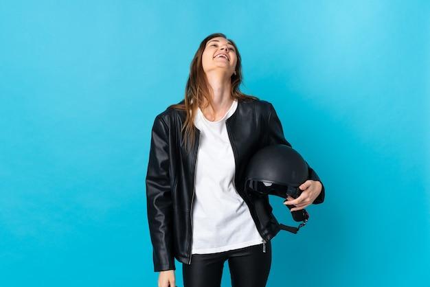 Jovem irlandesa segurando um capacete de motociclista isolado em um fundo azul rindo