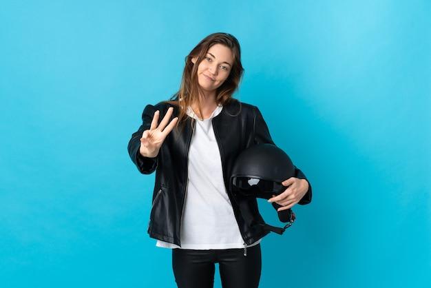 Jovem irlandesa segurando um capacete de motociclista isolado na parede azul feliz e contando três com os dedos