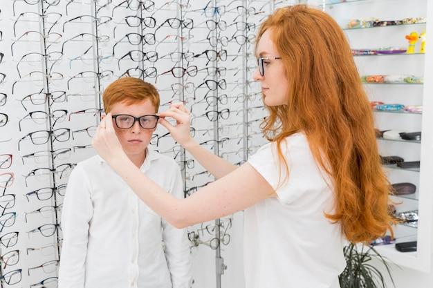 Jovem irmã usando óculos para o irmão na loja de óptica