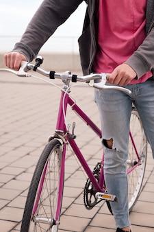 Jovem irreconhecível caminhando com uma bicicleta vintage