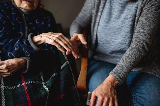 Jovem irreconhecível, de mãos dadas com a velha. filha se senta ao lado da velha mãe idosos, cuidado, conceito de família.