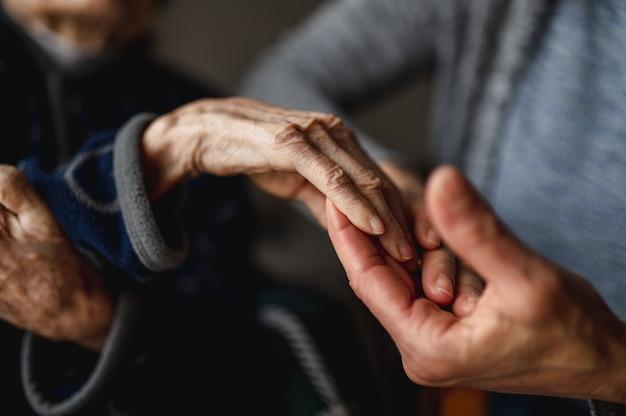 Jovem irreconhecível, de mãos dadas com a velha. idoso, cuidado, conceito de família.