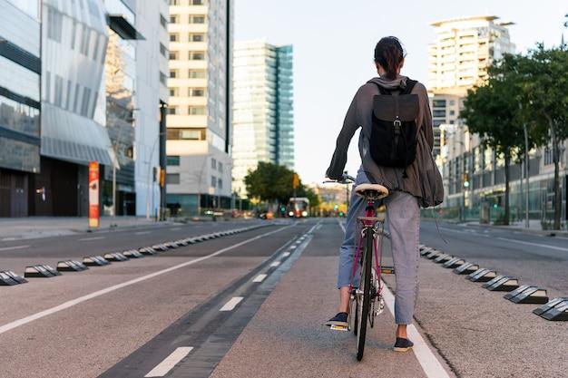 Jovem irreconhecível na cidade de bicicleta