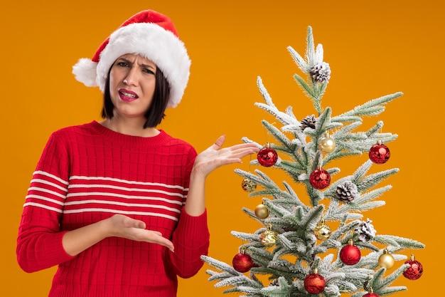 Jovem irritada com chapéu de papai noel em pé perto de uma árvore de natal decorada, olhando para a câmera apontando com as mãos para uma árvore isolada em fundo laranja