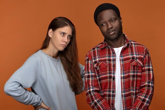 Jovem irritada e descontente com cabelo comprido olhando com raiva para o chateado namorado afro-americano que se esqueceu de seu aniversário. casal inter-racial com problemas e dificuldades de relacionamento