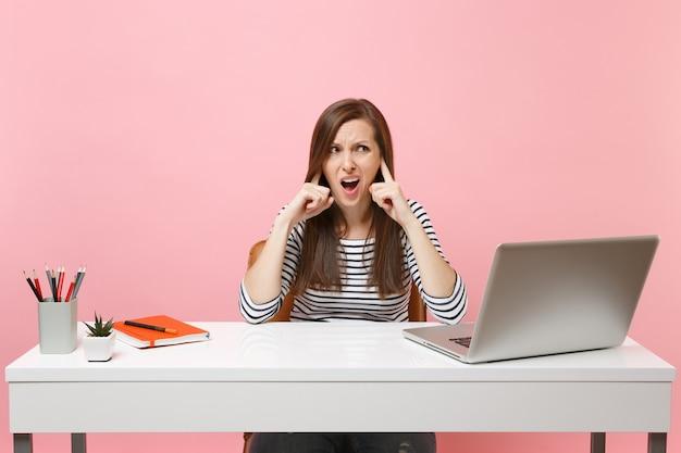 Jovem irritada mulher mal-humorada não quer ouvir cobrindo as orelhas com o dedo sentar no trabalho na mesa branca com o laptop pc contemporâneo isolado no fundo rosa. carreira empresarial de realização. copie o espaço.