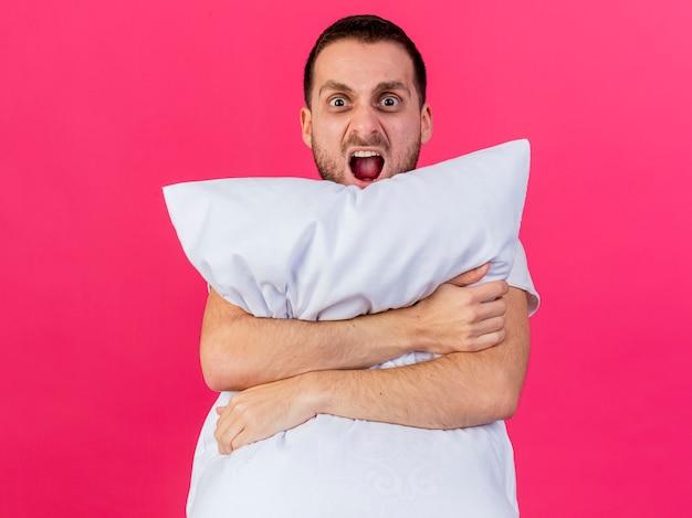 Jovem irritado abraçando o travesseiro isolado em rosa