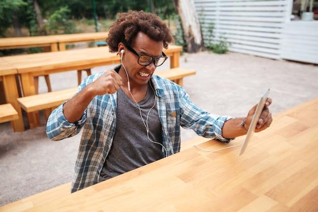 Jovem irritado com óculos e fones de ouvido usando tablet em um café ao ar livre