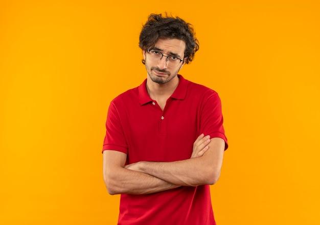 Jovem irritado com uma camisa vermelha e óculos ópticos cruzando os braços e parece isolado na parede laranja