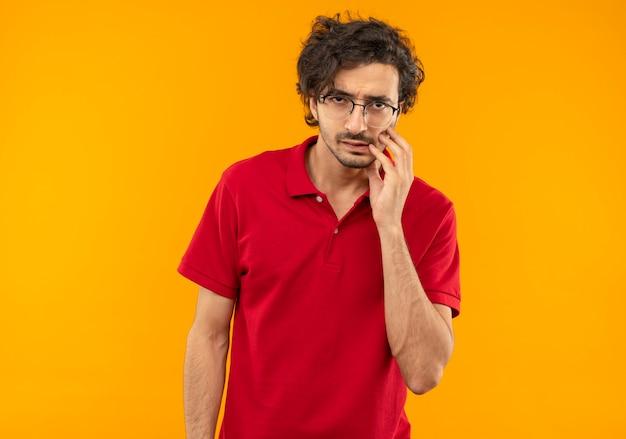 Jovem irritado com uma camisa vermelha e óculos óticos coloca a mão no rosto e parece isolado na parede laranja