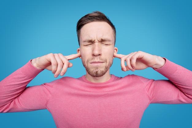 Jovem irritado em um pulôver rosa fechando as orelhas com os indicadores