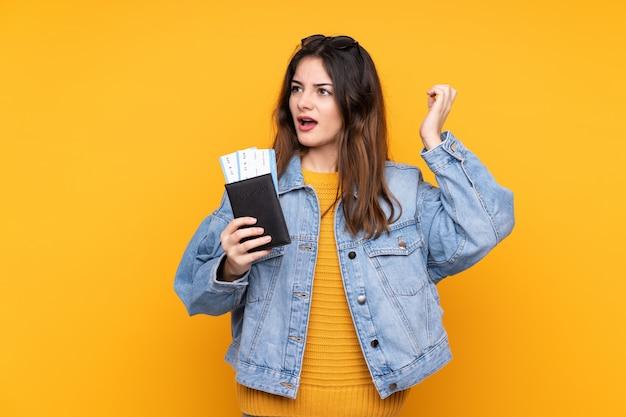 Jovem isolada na parede amarela em férias com bilhetes de avião e surpresa