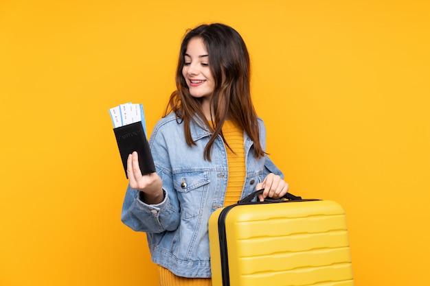 Jovem isolada na parede amarela em férias com mala e passaporte