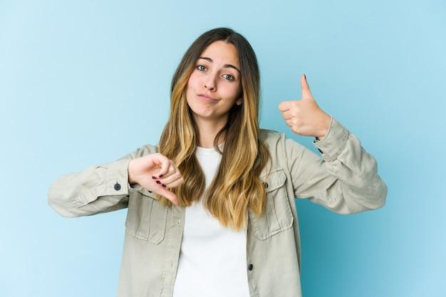 Jovem isolada na parede azul mostrando os polegares para cima e para baixo