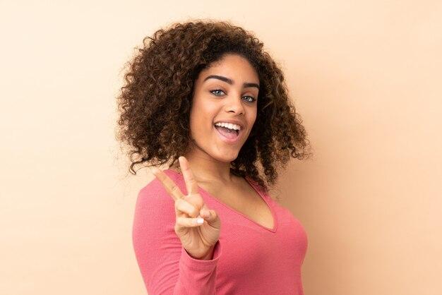 Jovem isolada na parede bege, sorrindo e mostrando sinal de vitória