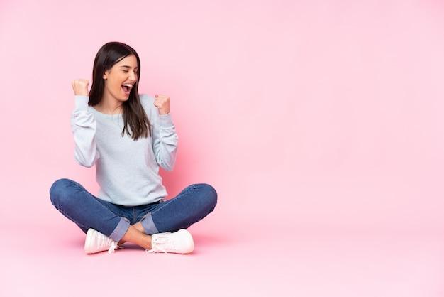 Jovem isolada na parede rosa comemorando uma vitória