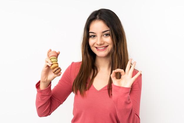 Jovem isolada na parede rosa segurando macarons franceses coloridos e mostrando sinal de ok com os dedos