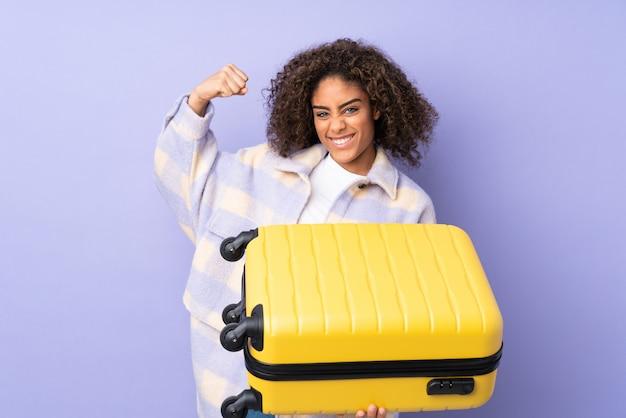 Jovem isolada na parede roxa em férias com mala de viagem