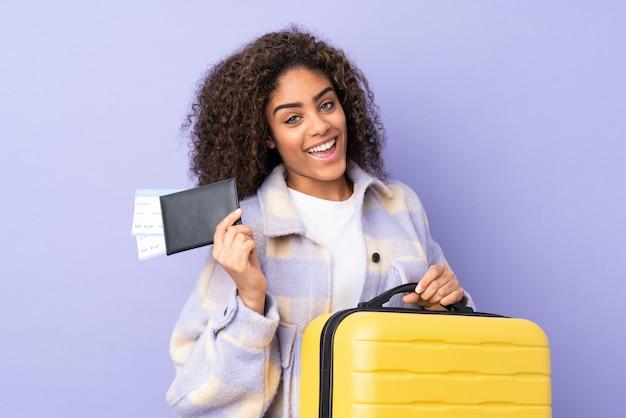 Jovem isolada na parede roxa em férias com mala e passaporte