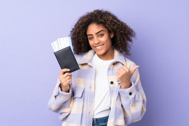 Jovem isolada na parede roxa em férias segurando um passaporte e avião com o polegar