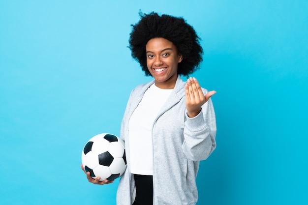Jovem isolada no azul com bola de futebol e fazendo gesto próximo