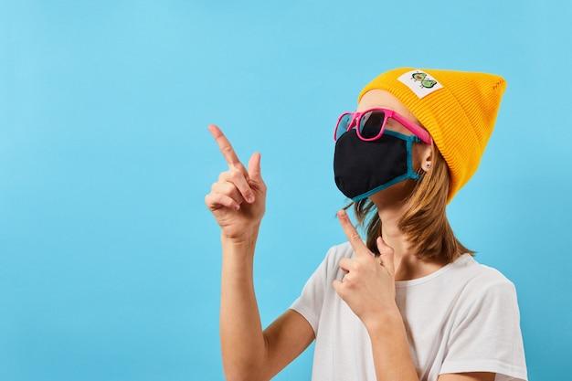 Jovem isolada sobre uma parede azul. adolescente mostrando copyspace apontando com a mão. adolescente hippie em óculos da moda, usando chapéu de malha com máscara protetora.