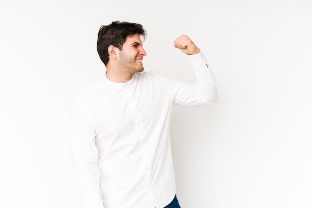 Jovem isolado no fundo branco comemorando uma vitória, paixão e entusiasmo, expressão feliz.