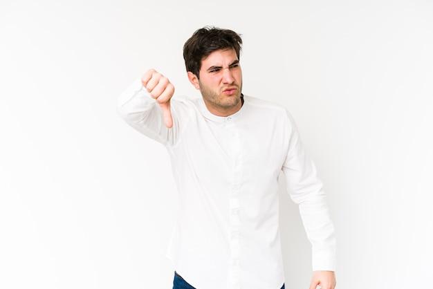 Jovem isolado no fundo branco, mostrando o polegar para baixo e expressando antipatia.