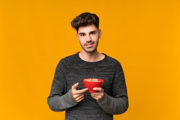 Jovem isolado segurando uma tigela de cereais