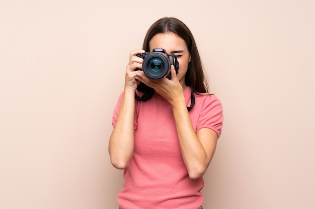 Jovem isolado sobre com uma câmera profissional