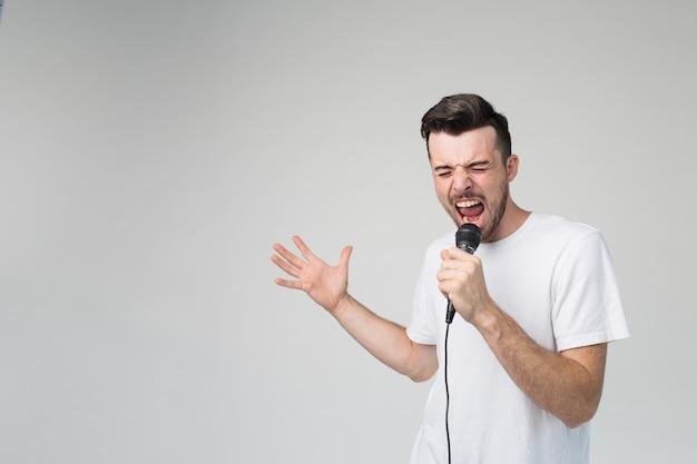 Jovem isolado sobre o fundo mantém o microfone na mão