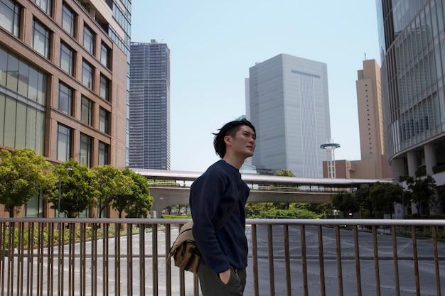 Jovem japonês com um suéter azul na cidade