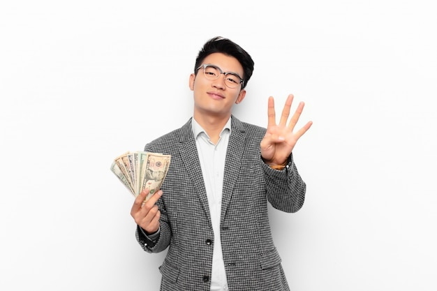 Jovem japonês sorrindo e olhando amigável, mostrando o número quatro ou quarto com a mão para a frente, contando para baixo. conceito de dinheiro