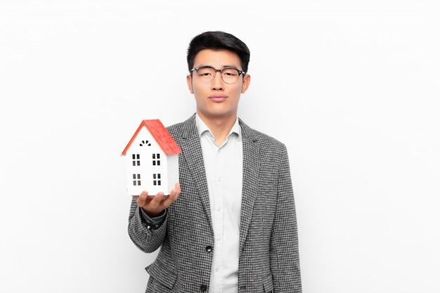 Jovem japonês triste e resmungão com um olhar infeliz, chorando com uma atitude negativa e frustrada com uma modelo de casa