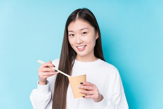 Jovem japonesa comendo macarrão