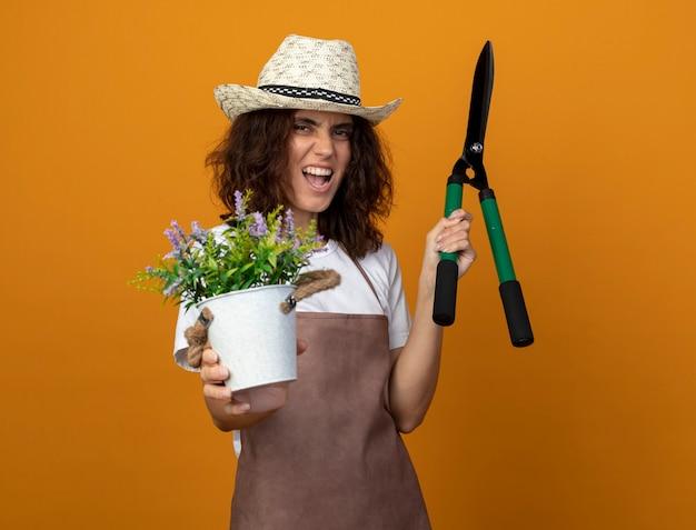 Jovem jardineira alegre de uniforme, usando um chapéu de jardinagem, segurando uma flor em um vaso de flores e segurando uma tesoura
