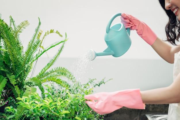 Jovem jardineira asiática usando telefone celular enquanto rega as plantas